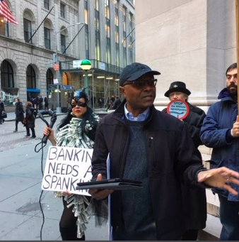 A new report from Rain Forest Action Network shows that JP Morgan Chase and other major banks are expanding their investment in fossil fuels despite the recent Paris Climate treaty. We hear from a press conference by Sane Energy outside the JP Morgan office across the street from the NY Stock Exchange on Wall Street.