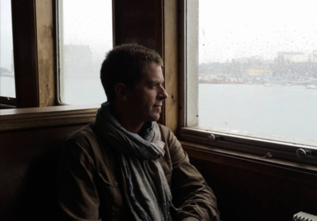 white man in scarf and jacket with short brown hair looks out of a window